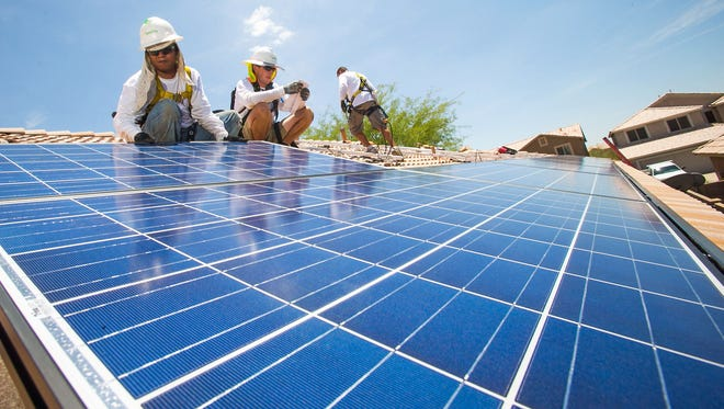 Workers install solar panels on a Cave Creek home in 2013.