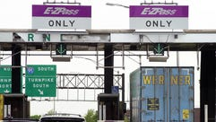 Cars and a truck go through the E-ZPass lanes at Exit