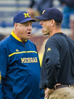 Michigan special teams coordinator John Baxter, left, and head coach Jim Harbaugh talk on the field before an NCAA college football game against Oregon State in Ann Arbor, Mich., Saturday, Sept. 12, 2015.