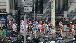 People flee the scene in Barcelona, Spain, Thursday,