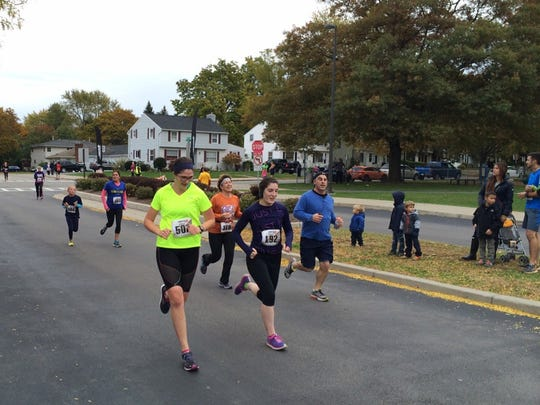 Runners power through the final stretch of the finish line of this 5K road race in East Rochester on Saturday, Oct. 24.