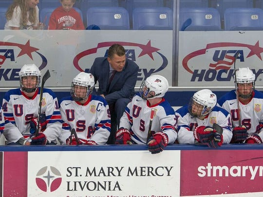 Seth Appert, new head coach of the USA Hockey NTDP Under-18 team, discusses in-game strategy with players during a recent preseason game.