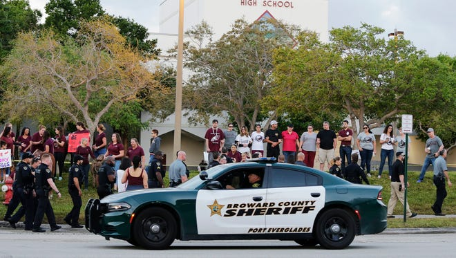 A police car drives by Marjory Stoneman Douglas High School in Parkland, Fla., Wednesday, Feb. 28, 2018. Students returned to class for the first time since a former student opened fire there with an assault weapon. (AP Photo/Terry Renna)