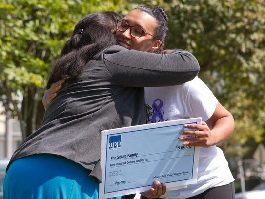 Alesha Williams-Boyd of the Asbury Park Press presents a check from the Helping Hands program to the Seidle children. Accepting the check is Kirsten Seidle, the eldest daughter of the family.