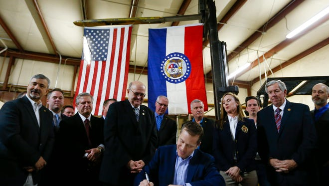 """Flanked by fellow lawmakers, Missouri Gov. Eric Greitens signs legislation to make Missouri the 28th """"right-to-work"""" state during a ceremonial signing at the abandoned Amelex warehouse in Springfield, Mo. on Monday, Feb. 6, 2017. The law, which goes into effect on Aug. 28, prohibits unions from charging membership dues as a condition of employment."""
