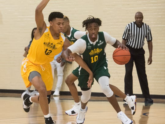 Shawndarius Cowart (No. 10) representing the West team drives up court during Friday night's Subway High School All-Star Basketball game at Pensacola State College against Aron Scott representing the East Team.