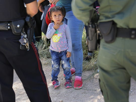 Una niña observa a un oficial de la Patrulla Fronteriza.