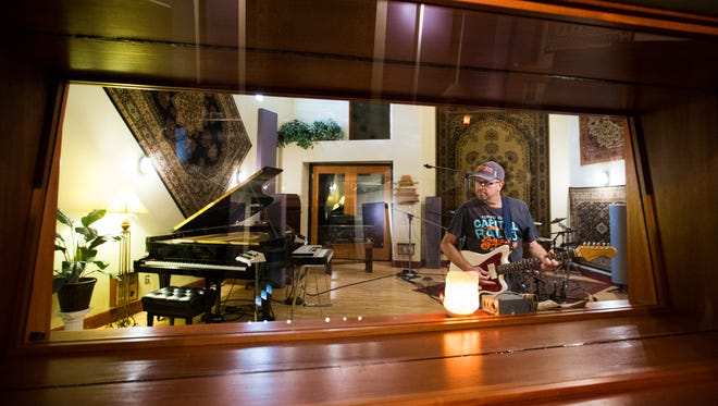 Owner Don Salter plays a guitar inside one of his four studios at the Saltmine Studio Oasis in Mesa. Salterâ??s downtown recording venue has hosted artists like DMX and Lil Wayne as well as various local musicians over the years.
