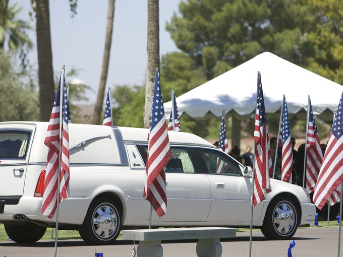 A hearse carrying the body of Chandler police detective
