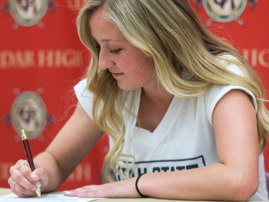 Cedar High School senior Tasha Kamachi signs a letter
