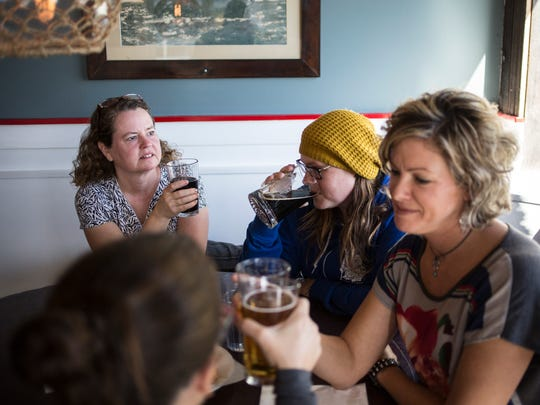 """Kristen Lyons, Missy Campau, Sheri Faust and Amy Meeker-Taylor hold a pose together at a table as part of a """"mannequin challenge"""" video Thursday, Nov, 10, 2016 at ThumbCoast Brewing Company in Port Huron. The video is part of a Blue Water Area Convention and Visitors Bureau effort to promote Port Huron."""