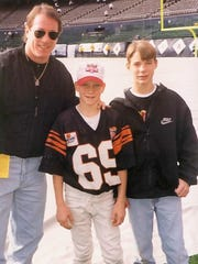 A young A.J. Hawk, center, earned his way to the national Punt, Pass and Kick competition in San Diego where he met Buffalo Bills quarterback Jim Kelly, left. His older brother Ryan, right, and the family made the trip as well.