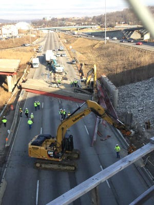 Workers using heavy equipment move cement barriers to open up a path at the scene of an I-75 overpass collapse near Cincinnati that killed one person Jan. 19, 2015.