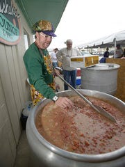 Krewe of Wrecks master bean cooker, Tommy Grice, cooks up the Mardi Gras favorite outside the Sandshaker during the annual red beans and rice luncheon on Pensacola Beach Monday morning Feb. 16, 2015.