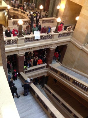 """Protesters surround the Assembly chamber at the state Capitol in Madison on Thursday, chanting """"Union busting is disgusting."""""""