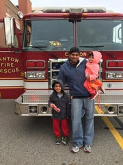 Ashish Patel, son Aayan, 31/2, and daughter Aanya, 2, stand in front of a Canton fire truck during their outing Saturday.