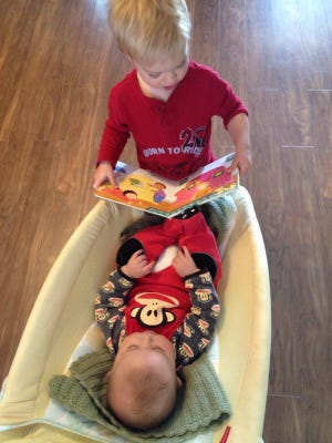 Brandon Johnson reads to his brother Colton Johnson from his new book he received through the Imagination Library.