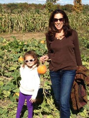 Barbara Adoff and her granddaughter, Iva, go pumpkin picking.