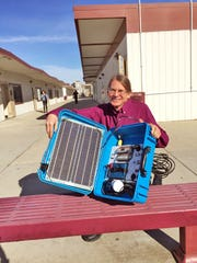 Salinas High instructor teacher Philip Deutschle shows off a solar suitcase after the ceremony on Thursday.