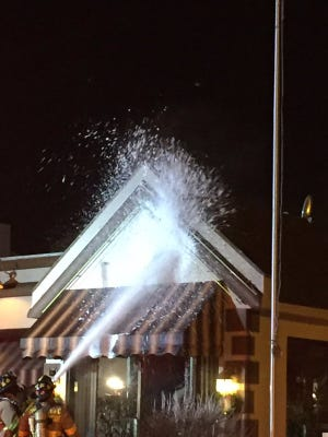 Fire crews extinguish a fire above the entrance of Rolling Meadows restaurant early Friday morning.