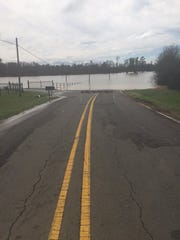 Flooding over a section of Wallace Lake Road obscures