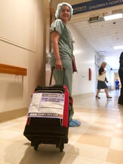 A nurse wheels a donated kidney from Jodi Schmidt at