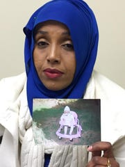 In this Monday, Jan. 30, 2017 photo, Samira Dahir holds up a picture of her daughter, Mushkaad, in Minneapolis. Dahir, who is Somali but also a  legal U.S. resident, became pregnant after she was granted refugee status and faced a gut-wrenching decision in 2013: Put her own resettlement on hold for several more years and re-apply with her daughter, or leave her little girl behind and try to bring her to the U.S. later.