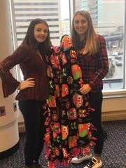 As part of the convention, students can donate fleece and make blankets as a service project. Pictured are Jasmine Owen and Macy Crump with the fleece blanket they made for Norton Children's Hospital.
