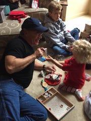 Evansville native Randy Demarest plays with his grandchildren.