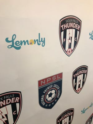 The Lemonly, Sioux Falls Thunder F.C. and National Premier Soccer League logos are on joint display in the backdrop for the Thunder's signing day, April 11.