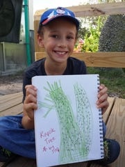 Joey Satery, 9. shows off a drawing of a kapok tree