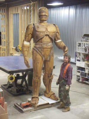In 2013, a craftsman from 3-D modeling company Across the Board Creations in Idaho stands next to the 10-foot model of the RoboCop statue.