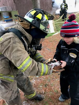 New Concord firefighter, Rebecca Spencer, hands puppies to Mason Williams after they were rescued from a burning barn.