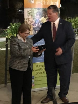 Devereux Community Based Care Chief Executive Officer Carol Deloach receives an award of recognition from Florida Coalition for Children Executive Director Kurt Kelly.