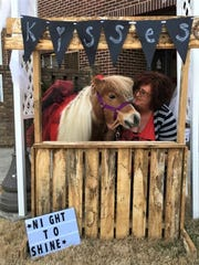 """Founder Angela Devine and Mocha manned the kissing booth at """"A Night to Shine,"""" a prom party for special education kids in February."""
