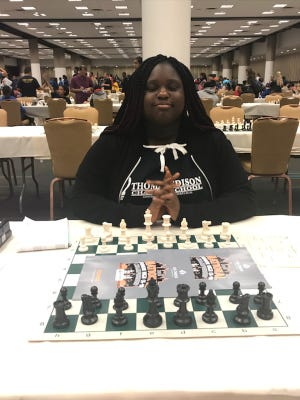 Serina Norwood, a 12-year-old member of the Thomas Edison Charter School chess team, in front of a chess board at the the 2018 National Junior High ChessChampionship in Atlanta.