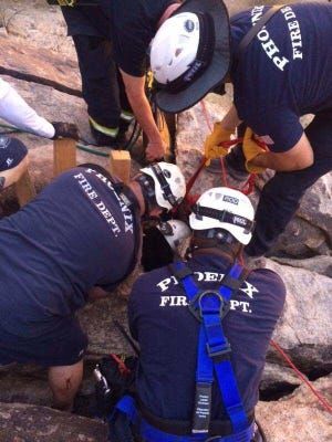 The woman was trapped while trying to find a pair of glasses that had fallen between the rocks.