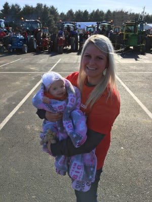 Amber Harrison holds her 8-month-old daughter, Hazel, with tractors parked behind them on Friday, April 20, 2018, in Auburndale. Hazel was born with a tumor on her heart and had a transplant in January. The Auburndale High School Tractor Club will donate money from its Bring Your Tractor to School Day parade to Hazel's family.