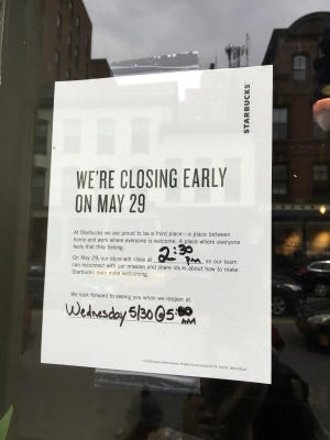 This Sunday, May 27, 2018, photo shows a sign displayed at a Starbucks cafe in Portland, Maine, reminding customers that the store will be closed Tuesday for training.