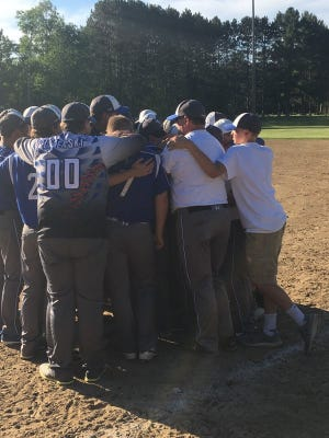 The Athens baseball team surrounds assistant coach Dale Westfall on Tuesday after their sectional final win on Tuesday. Westfall's son Tucker, 15, a member of the baseball team, died in a UTV crash on Saturday.