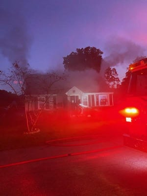 Firefighters arrived to heavy smoke coming from the eaves and second floor window of the home at 6 John St., Millbury, Monday evening, Oct. 5, 2020.