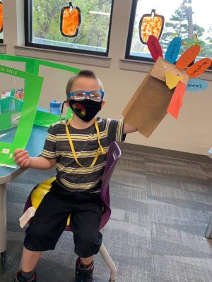 Logan Wall, a preschooler in Tanna Gassman's class at Shaner Early Learning Academy, shows off a paper bag turkey he made earlier in November.
