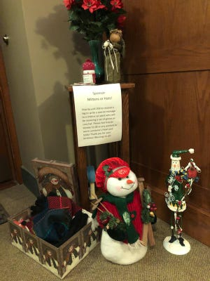 A collection box for hats, gloves and scarves sits outside Kathy Gentel's door at Midtown Village apartments.
