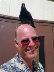 Foresta, a pet pigeon, sits a top Rob Freistadt's head at Central School Wednesday. The bird had disappeared Tuesday from Tara Atkins home in the Elkhorn Mountains near Montana City. But it was back in her arms on Wednesday after it showed up at her school about 5 air miles away in Helena. The bird sat on the head of Central-Linc Elementary teacher Freistadt. Principal Vanessa Nasset asked Tara for help catching Foresta after a parent remembered she had a pet pigeon.