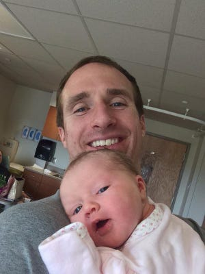 Drew Brees holds his daughter, born Monday.