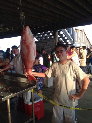 Nathaniel Guy, 12, poses next to his division-winning red snapper.