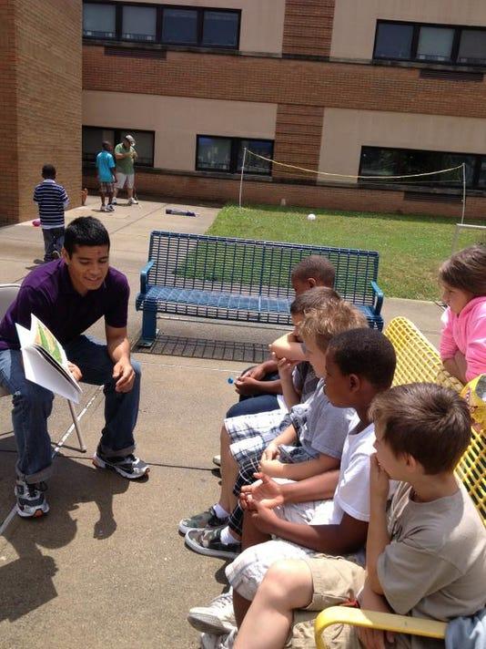 A volunteer reads to kids.JPG