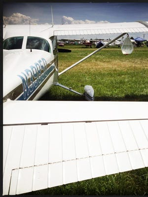 A bag of water hangs from the wing of an airplane at EAA AirVenture 2013.