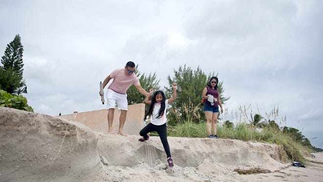 Jose and Jayla, 7, Lopez, and Jeanette Perez, all from West Palm Beach, climb down a drop-off caused by erosion from Hurricane Dorian at the beach near Reef Road Wednesday September 4, 2019 in Palm Beach.