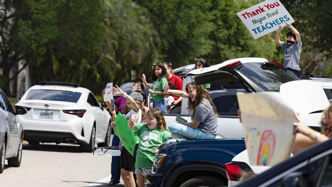 Students and parents of children at Hagen Road Elementary wave to teachers along a parade route during the extended spring break caused by the coronavirus outbreak. Teachers of Hagen Road Elementary planned a socially-distant car parade to boost school and community morale in Boynton Beach, Wednesday, March 25, 2020.